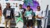 Algarvio Francisco Duarte, segurando a prancha com X verde, no pódio Surf Open na Praia das Bicas (®SCS)