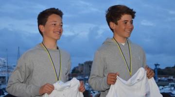 Após a penúltima prova do circuito espanhol Optimist Excellence Cup 2017-2018, Guilherme Cavaci, à direita, é 2º na geral; e William Risselin, à esquerda, é 3º geral, 1º Sub-15 Masculino (®PauloMarcelino/arquivo)