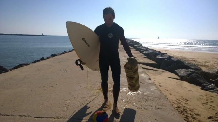 Surfista carrega bóia de navio retirada da Praia da Rocha (®JoãoBrekBracourt)